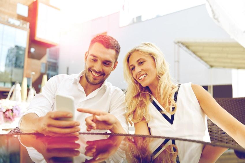 Junges paar mit Handy auf der Restaurant Terrasse