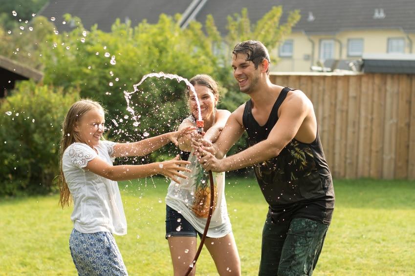 Junge Familie spielt und spritzt mit Gartenschlauch umher