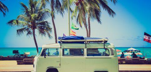 VW-Bus vor Palmen, gepackt für die Urlaubsreise
