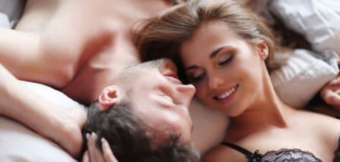 hübsches junges Paar liegt im Bett Kopf an Kopf und ist zärtlich miteinander