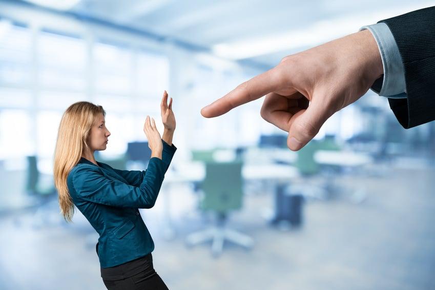 Männlicher Zeigefinger der drohend auf Angestellte deutet