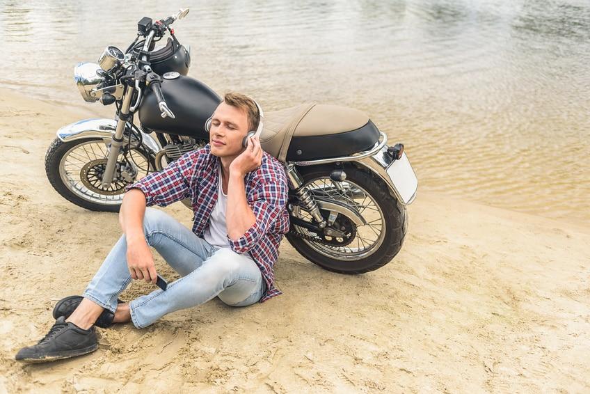 ein junger Mann sitzt vor seinem Retro-Motorrad und genießt mit geschlossenen Augen Musik über Kopfhörer