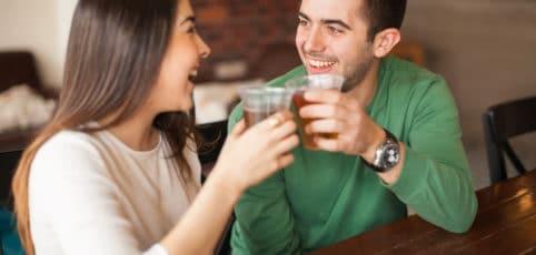 Junge Frau und junger Mann sitzen im Café und unterhalten sich beim ersten Date