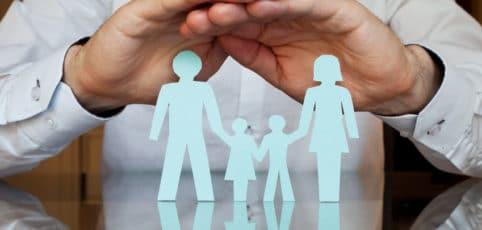 Mann hält seine Hände schützend über eine Familie aus Papier die sich an den Händen hält
