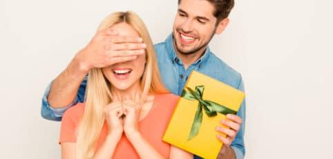 Mann mit Geschenk hält seiner Freundin die Augen zu