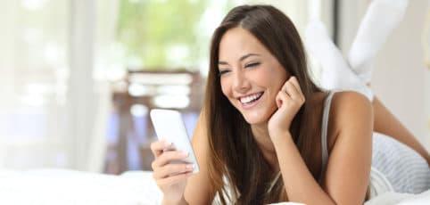 Junge hübsche Frau liegt auf dem Bett und chattet mit dem Smartphone