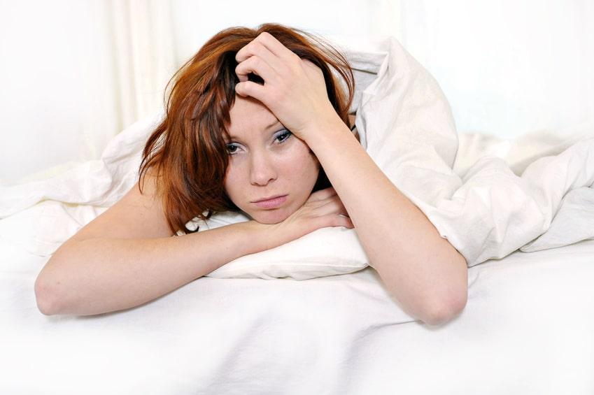 junge Frau liegt im Bett und hält sich den Kopf nach durchzechter Nacht