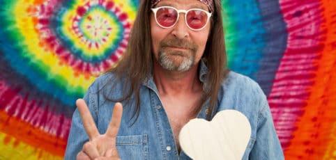 Älterer männlicher Hippie vor bunten Batiktuch und Peace Zeichen mit einer Hand