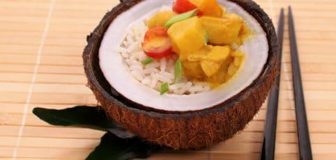 leckeres Mango-Gericht in Kokosnusshälfte angerichtet