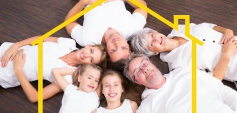 Die ganze Familie liegt am Boden, Kopf an Kopf und kuckt in die Kamera
