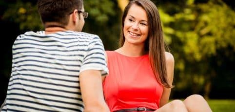 junges Paar sitzt auf der Wiese