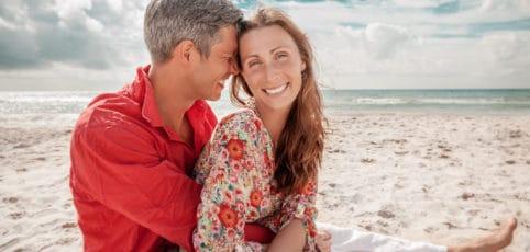 junges verliebtes Paar sitzt am Strand genießt die Sonne und das Meer