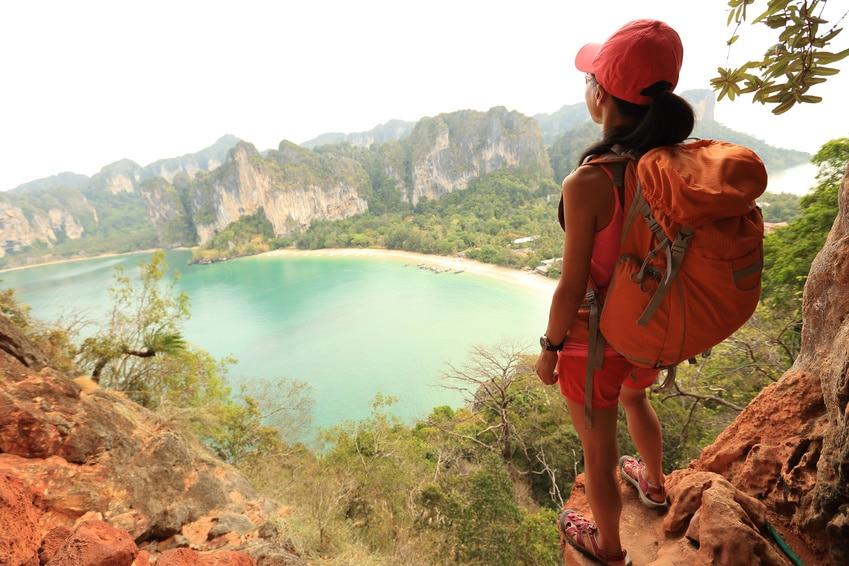 junge Frau mit Rucksack steht auf einem Felsen und kuckt tief runter auf einen See