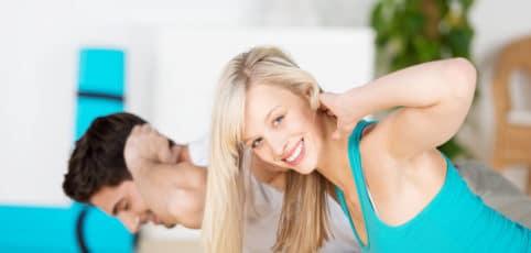 eine lächelnde Frau beim Training mit den Händen hinter dem Kopf