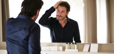 attraktiver Mann betrachtet sich im Spiegel