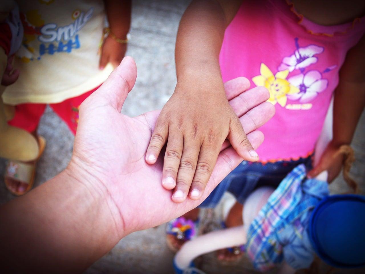 Kinderhand in der Hand eines Erwachsenen