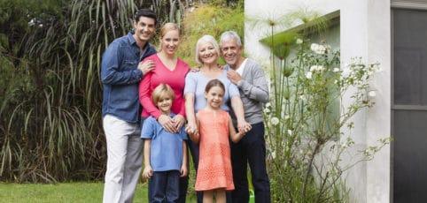 Eine ganze Generation Familie steht im Garten und lächelt