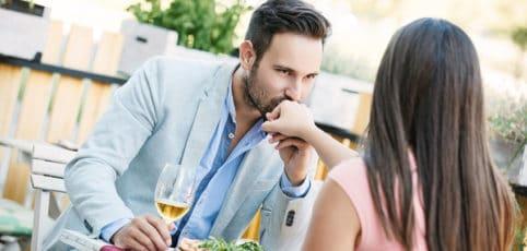 attraktiver Mann küßt seiner Begleitung die Hand im Restaurant