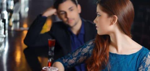 Blickkontakt an der Bar von attraktiver Frau mit jungen Mann