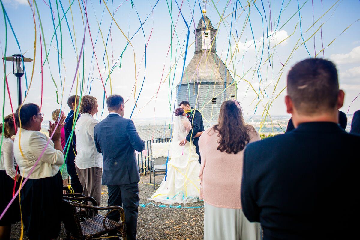 Hochzeitsgruppe steht im Freien vor einer Kapelle
