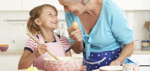 Großmama und Enkelin backen in der Küche zusammen einen Kuchen