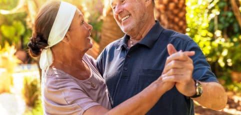 älteres Paar tanzt fröhlich unter Palmen