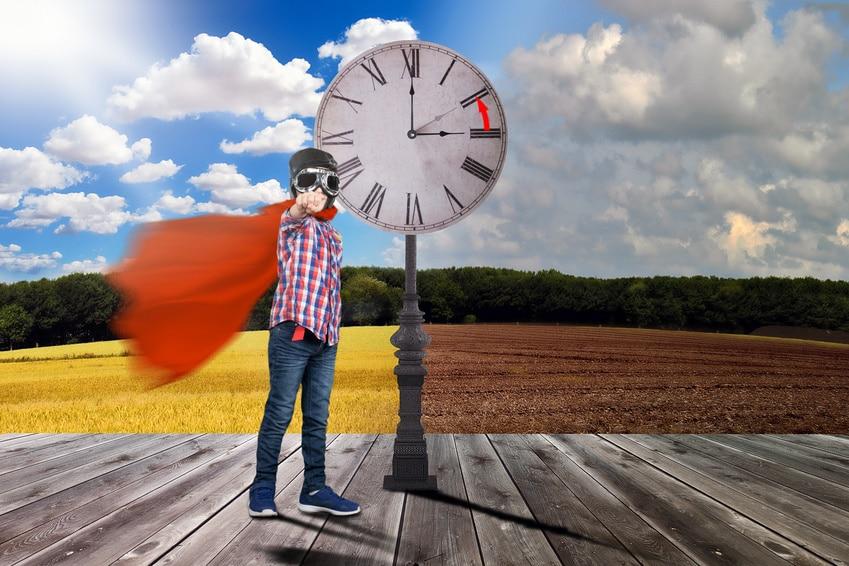 Junge mit rotem Umhang und Fliegerbrille in Supermann Stellung an einem Bahnsteig mit einer großen Uhr, im Hintergrund Sommer und Winter