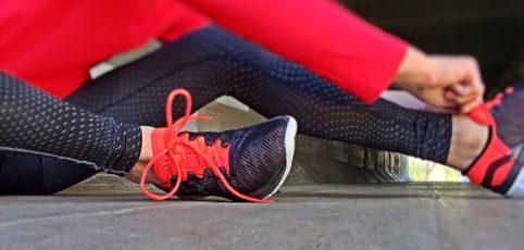 Frau zieht ihre Sportschuhe fürs Training an