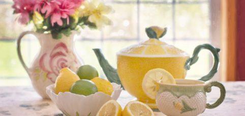 Teekanne die aussieht wie eine Zitrone und halbierte Zitronen davor
