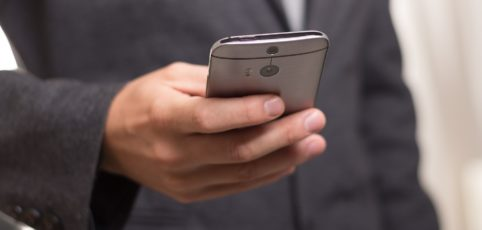 Mann mit Handy der gerade eine sms schreibt