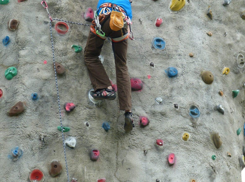 Sportler an der Kletterwand am üben