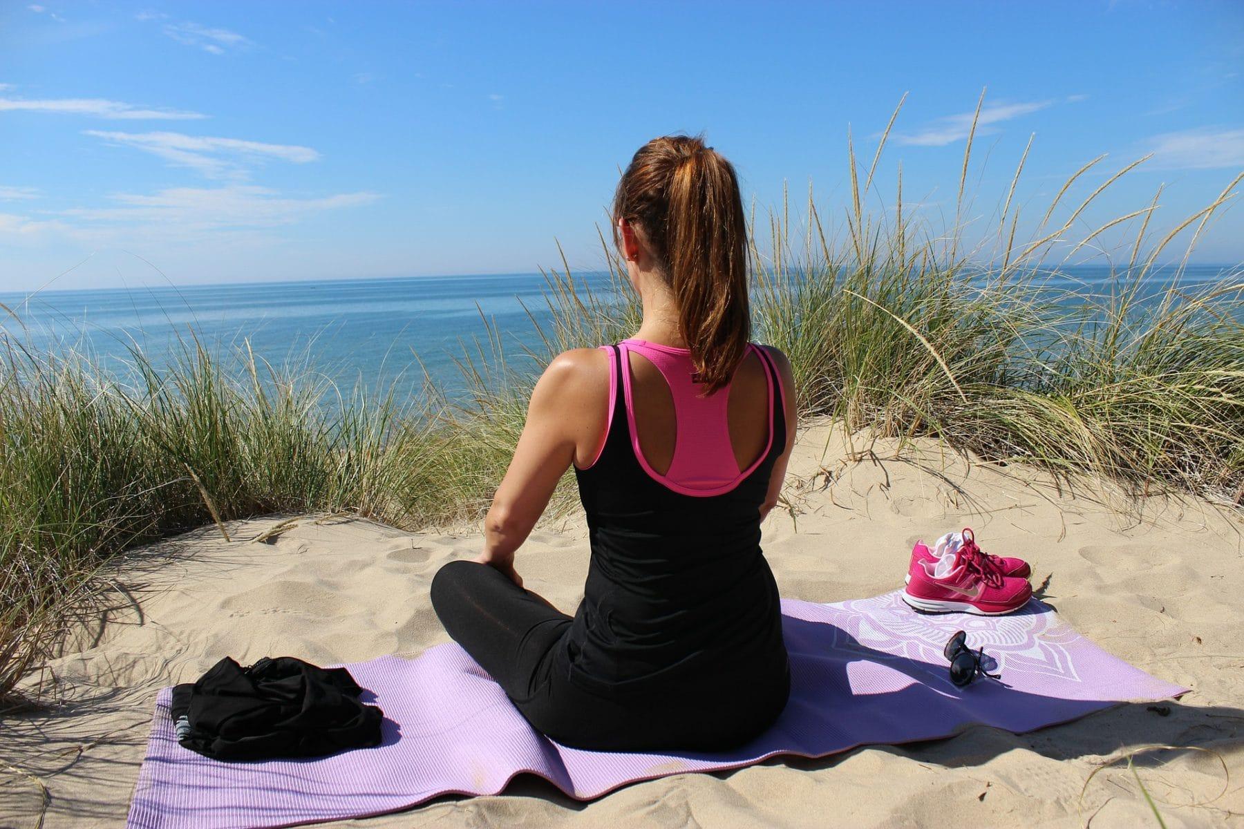 Frau auf einer Düne auf Yogamatte sitzend mit Blick zum Meer