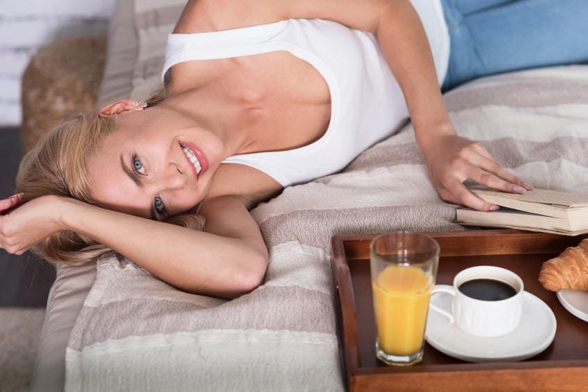 Blonde Frau liest im Bett ein Buch