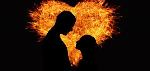 Flammendes Herz mit Liebespaar als Silhouette in der Mitte