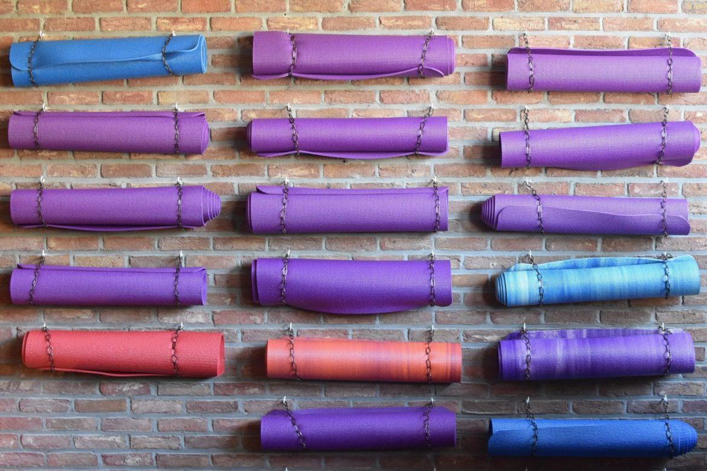 Yogamatten, zusammengerollt an eine Ziegelmauer gehängt
