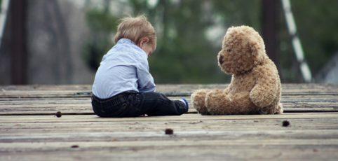 Baby sitzt am Holzsteg mit Teddy gegenüber
