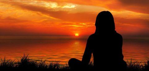 Frau sitzt im Sonnenuntergang am See und blickt über das Wasser