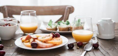 Lecker gedeckter Frühstückstisch mit Obst, Orangensaft, Frischkäsebrötchen und Kaffee