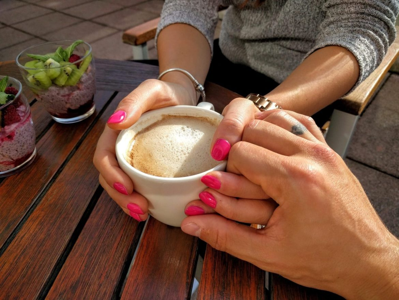 Frau hält sich an Kaffeetasse fest und Mann legt seine Hand auf ihre