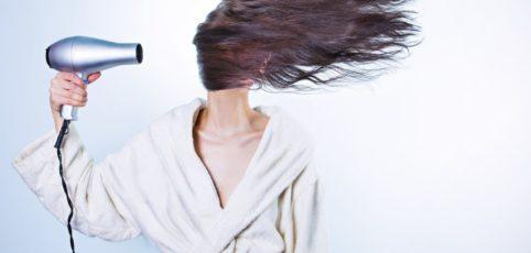 Frau föhnt ihr langes Haar und die gehen komplett über das Gesicht