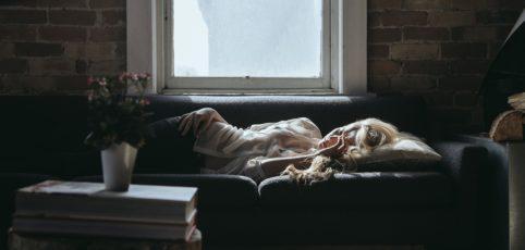 Frau auf dem Sofa am Morgen nach einer langen Nacht