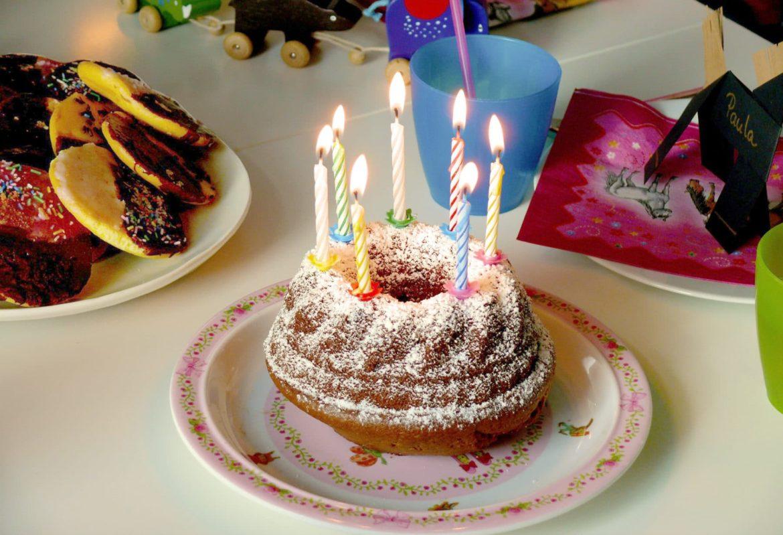 Gugelhupf mit Puderzucker und brennenden Kerzen auf gedecktem Tisch für den Kindergeburtstag