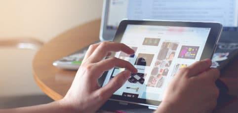 Frau sieht sich auf dem iPad Internetseiten mit Vorschlägen zu Modestyles an
