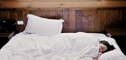 Frau eingemummelt in Bettdecke im Schlafzimmer mit Oberlicht