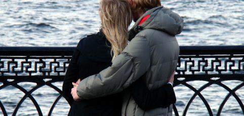 Paar umart sich und blickt aufs Wasser