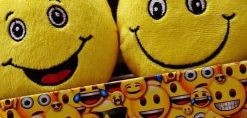 Zwei lustige Smileys schauen aus einer Geschenkbox