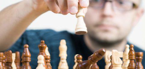 Schachspieler spielt Schachzug und schlägt den gegnerischen Springer
