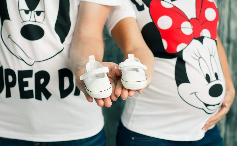 junges Paar, sie schwanger, beide mit Micky Maus T-Shirts und jeder einen Babyschuh auf der Hand