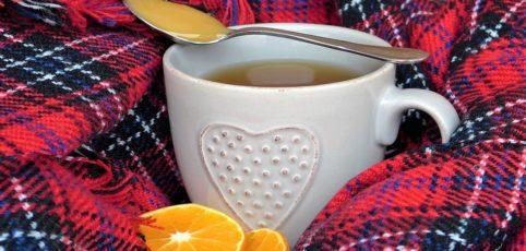 Tasse Tee mit einem Löffel Honig und Orangenscheiben