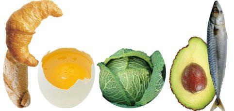 ein Croissant, ein offenes Ei, ein Wirsing, eine Avocado halbiert und ein Fisch, alles nebeneinander